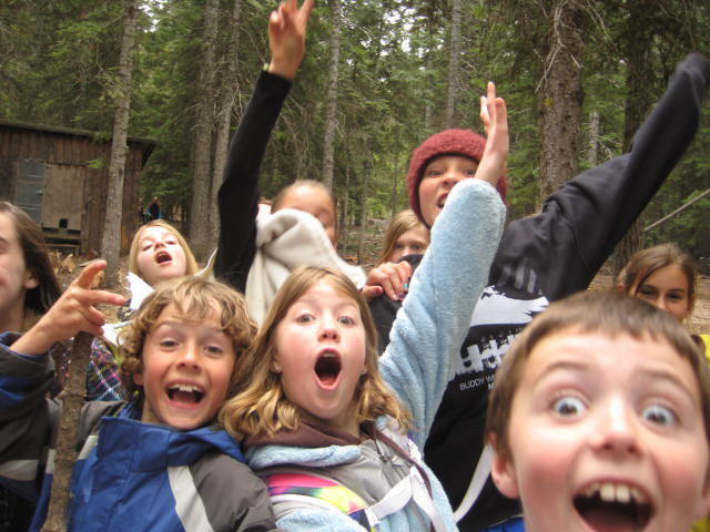 Excited kids outdoors raising hands