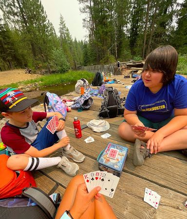 Ian, (NIT) playing cards with campers